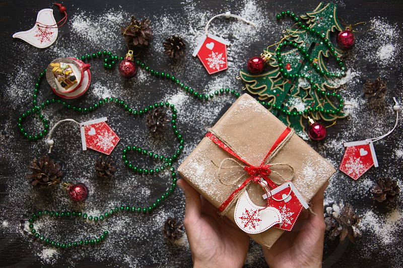 Still life with giftbox and Christmas toys on dark wooden background photo