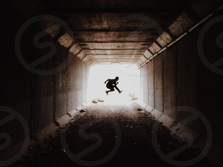 person jumping in a tunnel photo