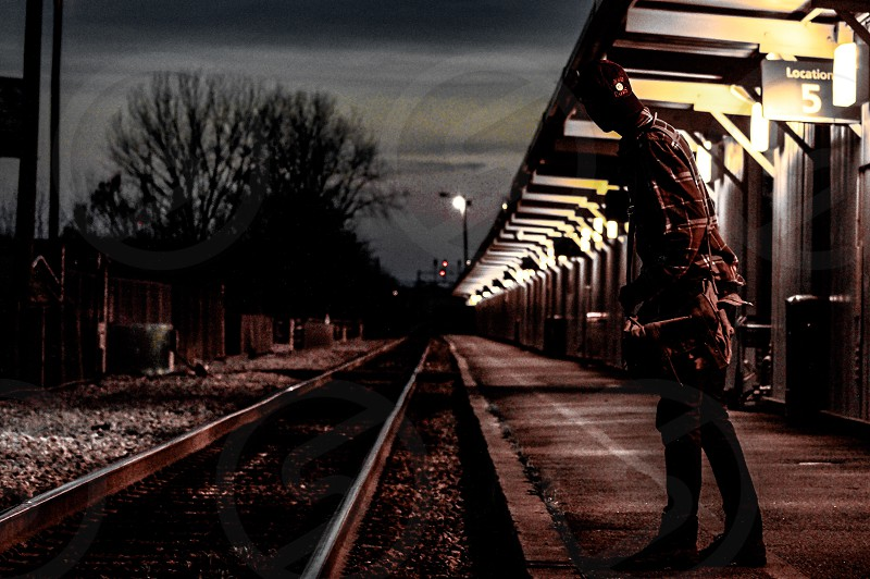 person wearing brown shirt standing on train way during nighttime photo
