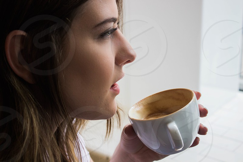 woman holding white ceramic cup standing beside window during daytime photo