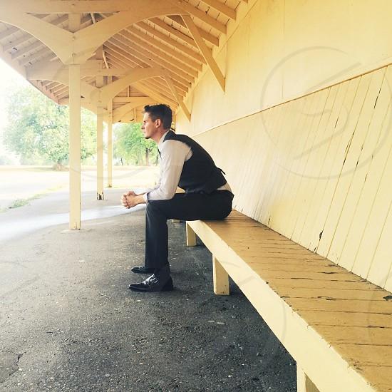 man in slacks and vest sitting on long bench under overhang photo