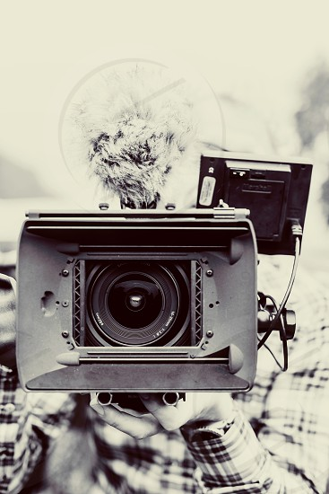 Monochrome picture of a cameraman filming in your face photo
