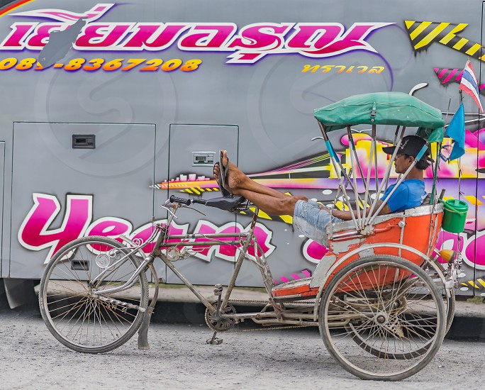 A Thai rickshaw driver relaxes while he waits for customers. photo