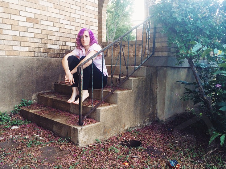 woman sitting on concrete stairs near green plant photo