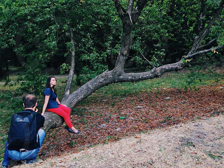 man in black t-shirt with black backpack taking picture of woman in blue shirt sitting on brown tree trunk during daytime photo