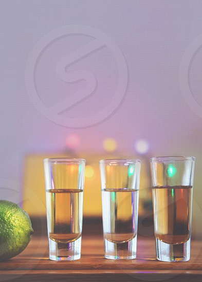 3 tequila single shot glass with content near lemon on brown wooden table photo