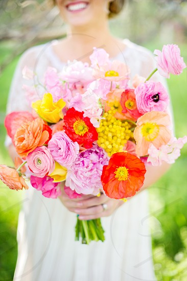 Bride smiling holding colorful spring bridal bouquet with poppies and ranunculus  photo