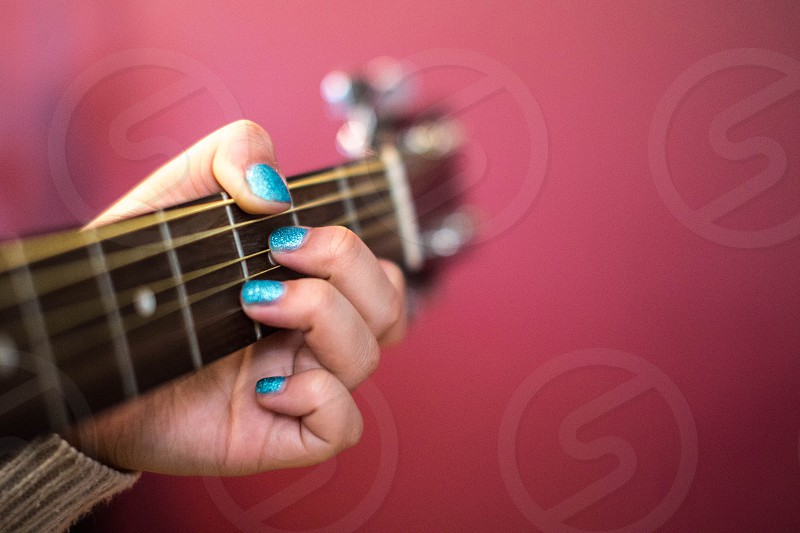 woman in blue glitters nail manicure playing guitar photo