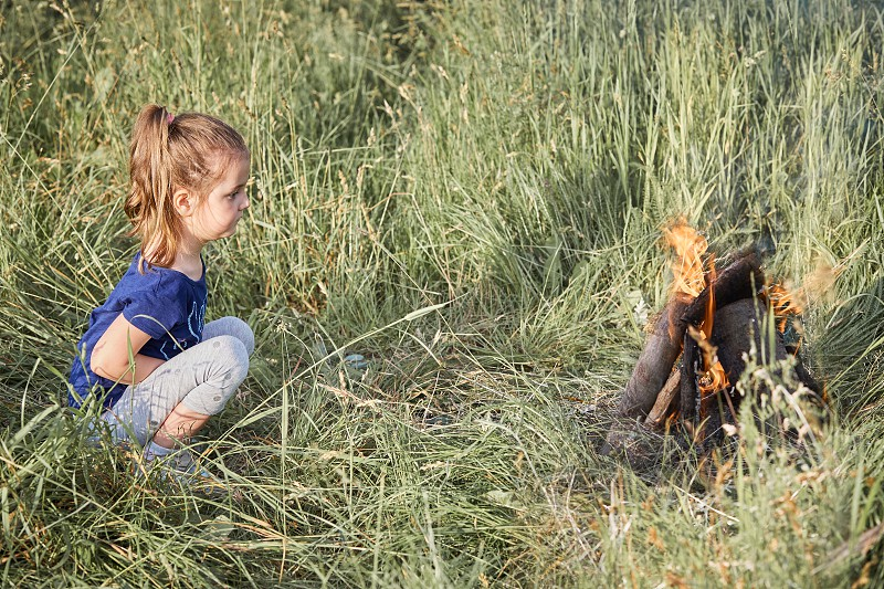 Little girl looking at campfire sitting in a grass. Candid people real moments authentic situations photo