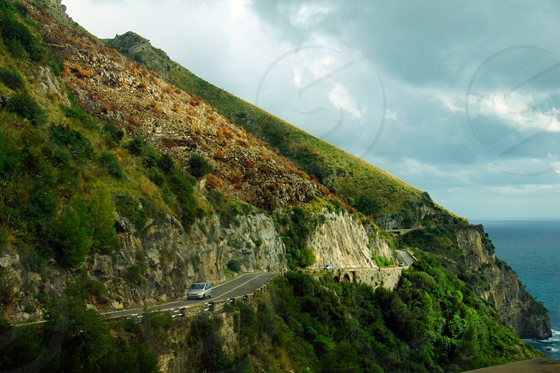grey concrete road on the side of a mountain with green bush under blue sky photo