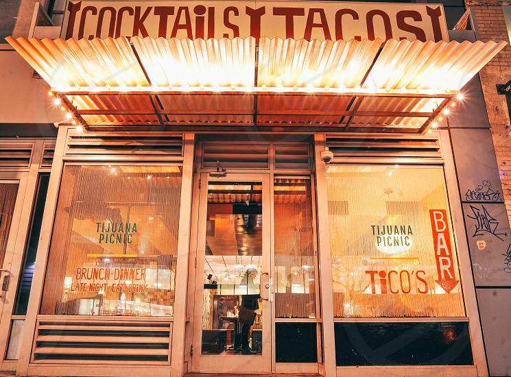 cocktails tacos sign above a tijuana tacos restaurant glass front photo
