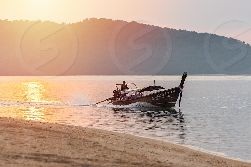 Nopparat Thara Krabi Province Thailand - January 14 2019:  One men on thai long-tail motor boat floats in sea water in the evening from touristic day tour to the local islands photo