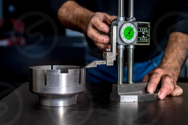 Quality Assurance. Worker's hands using precision venirs to measure the height tolerance of a manufactured metal part in a quality control environment. photo
