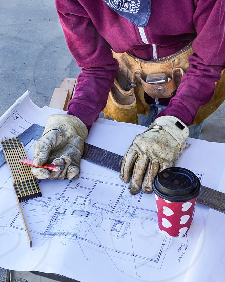 Portrait without a Face: Female carpenter checks measurements on an architectural plan on a construction site cup of coffee square ruler photo