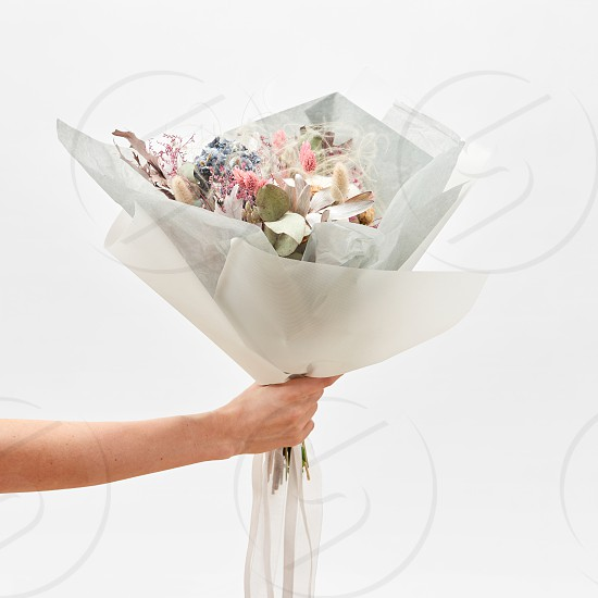 Woman's hand holds congratulation bunch from beautiful flowers on a light grey background with copy space. Wedding bouquet concept. photo