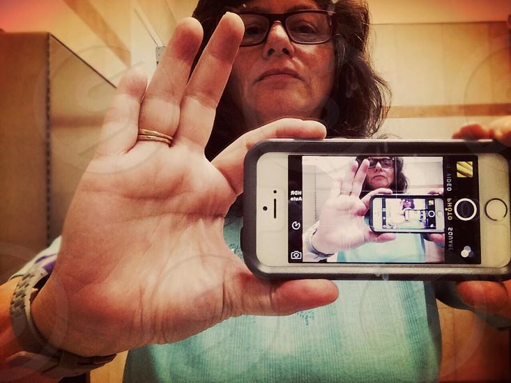 woman wearing teal top taking selfie photo
