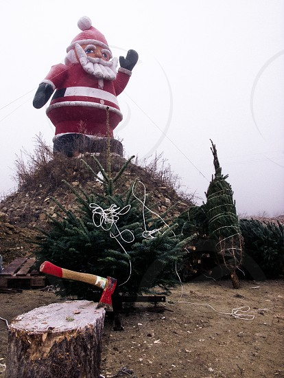 inflatable Santa Christmas tree axe rope absurd winter fog photo