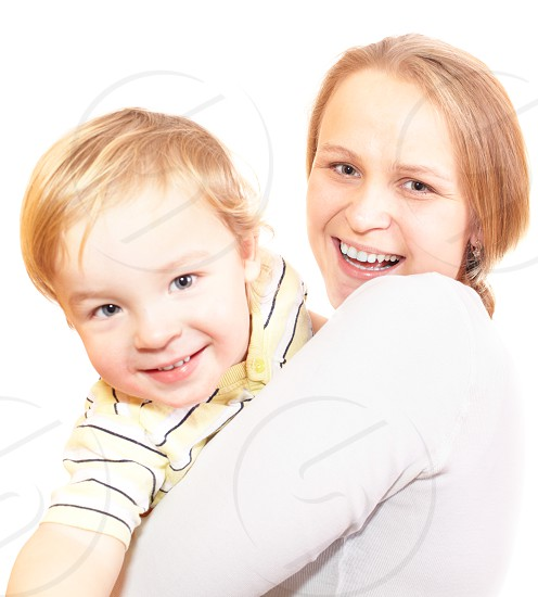 Young mother with her son are hugging and laughing. Focus is on the mother's face. Shallow dof. Isolated on white. photo