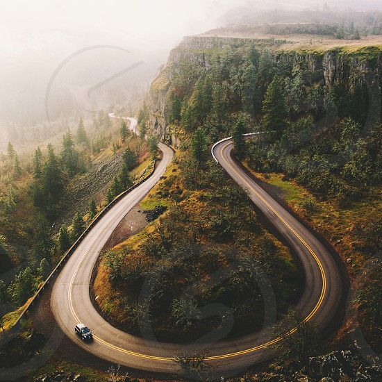 car passing on curved road on mountain slope with green trees top view photo