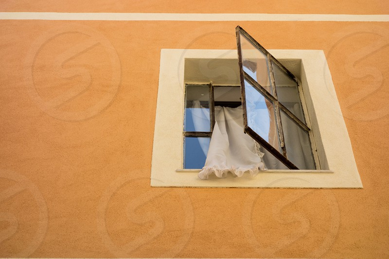 View up to a white framed open window with a a curtain hanging out set in a yellowy orange wall... photo