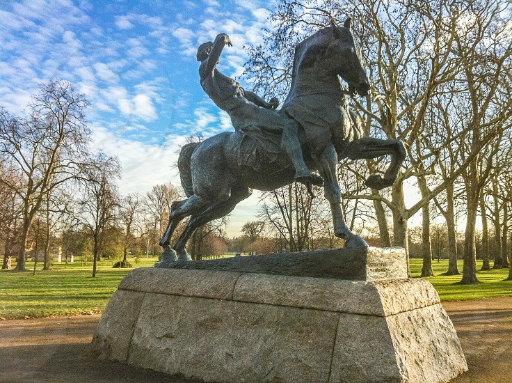 low angle photo of man riding horse statue with background of leafless trees photo