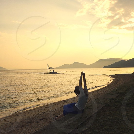 woman sitting stretching facing sea photo