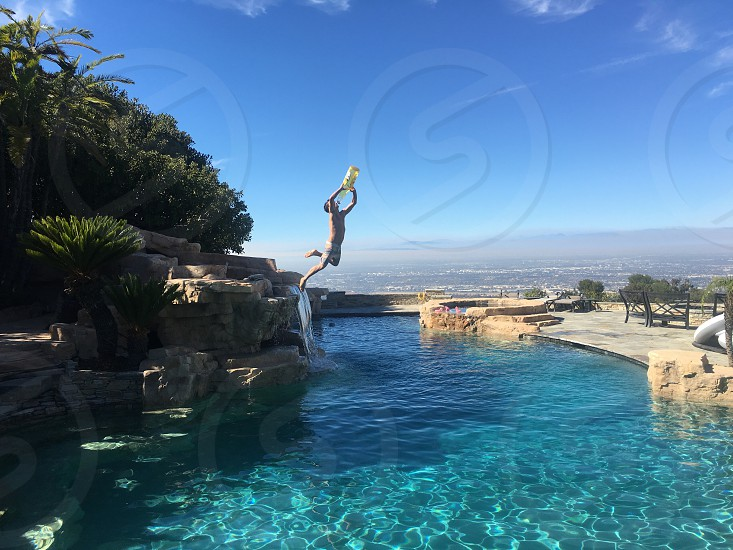 boy in white shorts holding yellow plastic container jumping on swimming pool during daytime photo