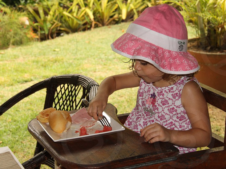baby girl wearing pink hat eating meal on high chair photo