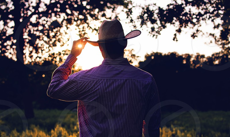 Scenic inspirational image of man in cowboy hat gazing toward the peaceful scenic sunset.   photo