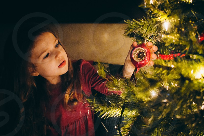 girl with brown long hair in red blouse touching red bauble hanging on green christmas tree photo