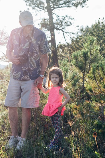 man and girl holding standing near small tree photograph photo