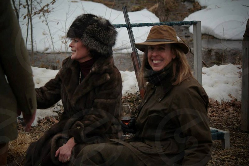 two females in black jackets with hats in snow landscape photo