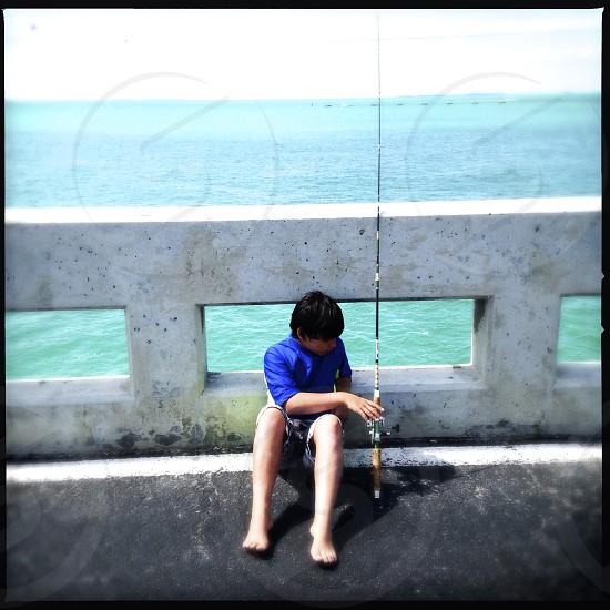 little boy fishing off bridge in key west florida / USA photo