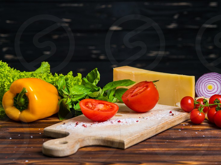 wooden board with parmesan cheese fresh cherry tomatoes lettuce sea salt paprika and yellow bulgarian pepper red onion. Appetizing still life from vegetables photo