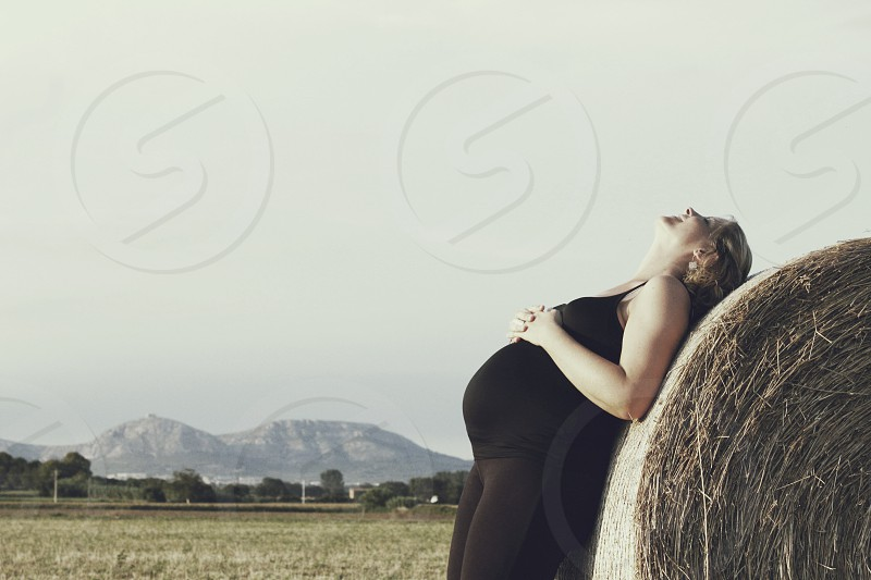 pregnant woman leaning against a hay bale photo