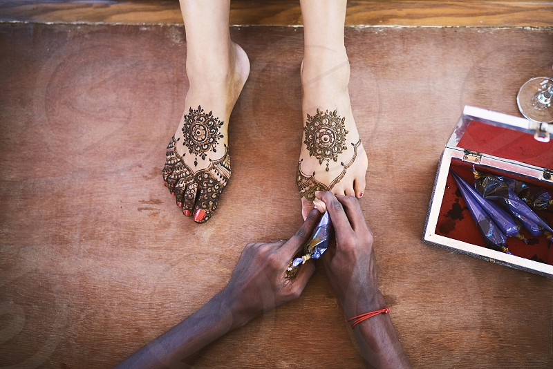 The Indian henna artist drawing the tattoo art (Mehndi) on the women foot on the indian wedding day photo