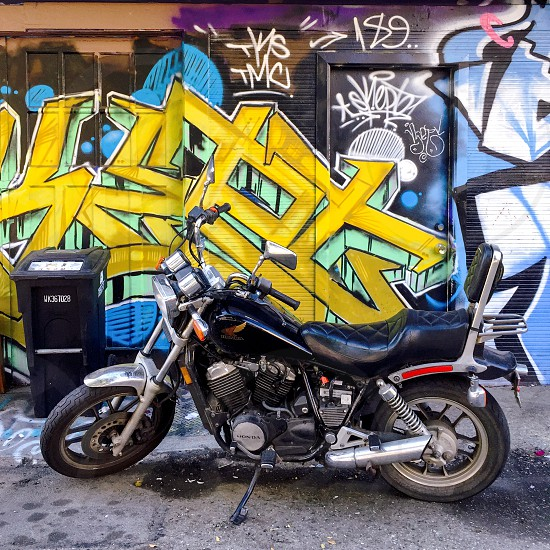Motorcycle in front of graffiti wall.  photo