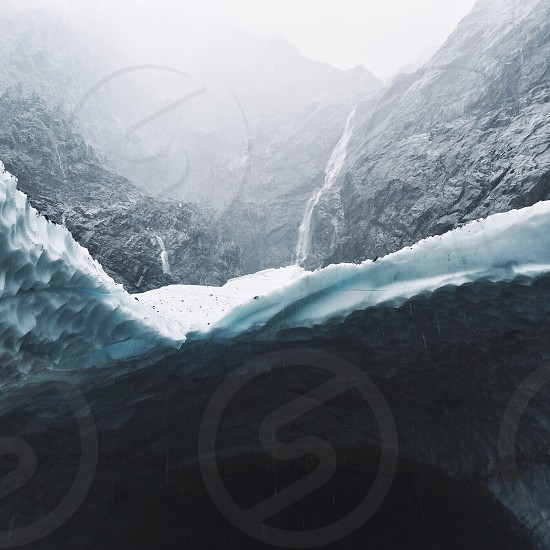 grey rocky cave covered in ice photo