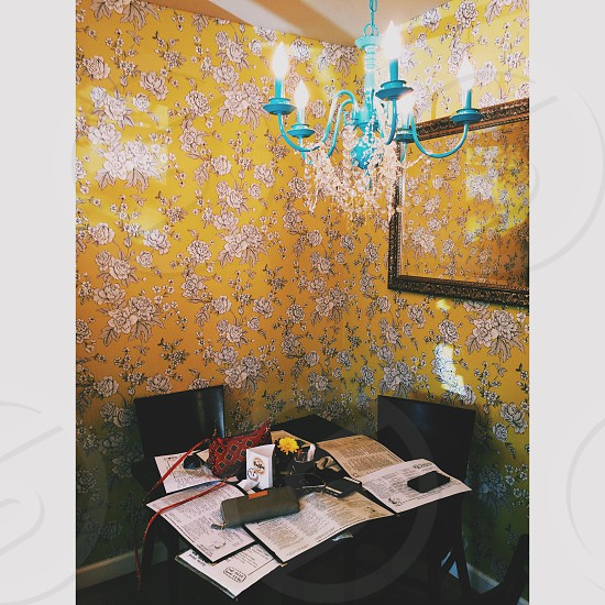 small dining table in a room with yellow wallpaper and a blue chandelier photo
