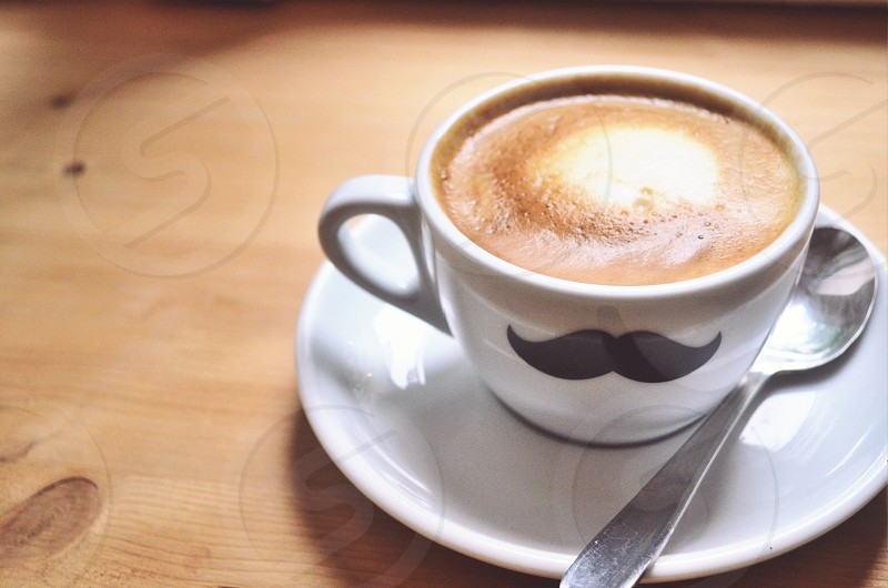 Mustache cappuccino on a saucer with spoon photo
