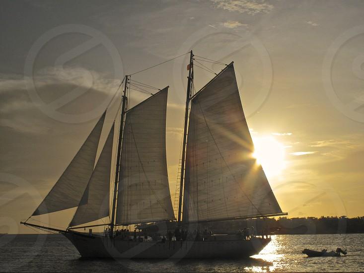 sailing at sunset sails boating dusk rays of sun photo