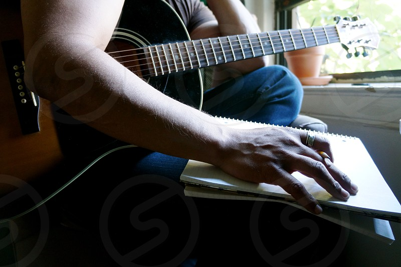 Person Holding Guitar and Notebook photo