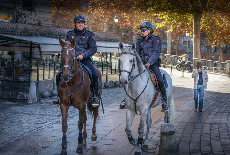 Glimpse of horse-riden policemen guarding the city in Madrid Spain photo