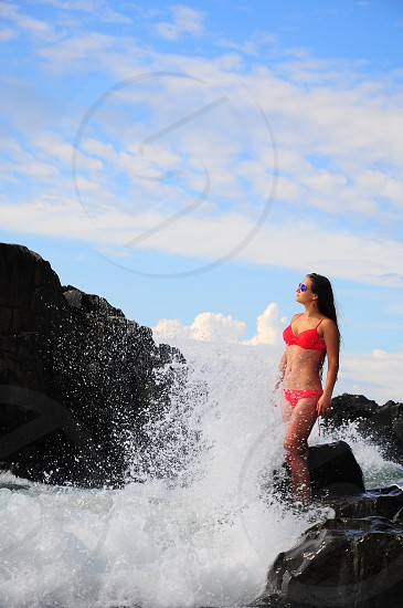 woman wearing red 2 piece bikini top and bottom blue sunglasses standing in rock in front of sea waves photo