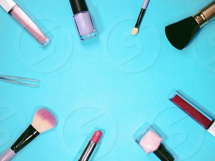 set of professional decorative cosmetics makeup tools and accessory on blue background with copy space for text. beauty fashion party and shopping concept. flat lay frame composition top view photo