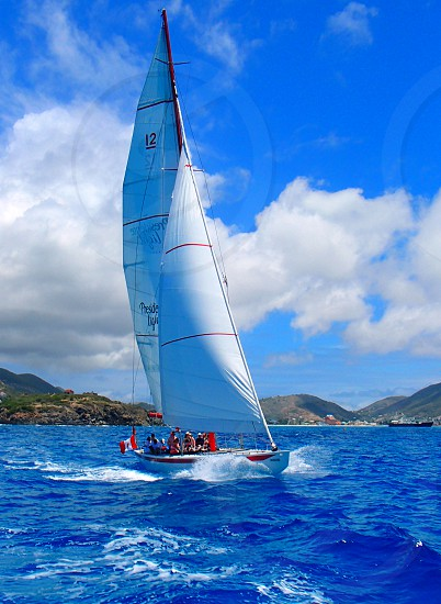 white 12 sailboat on blue body of water near mountains photo