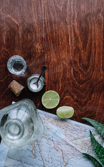sliced lime beside jar with salt inside on brown wooden table photo