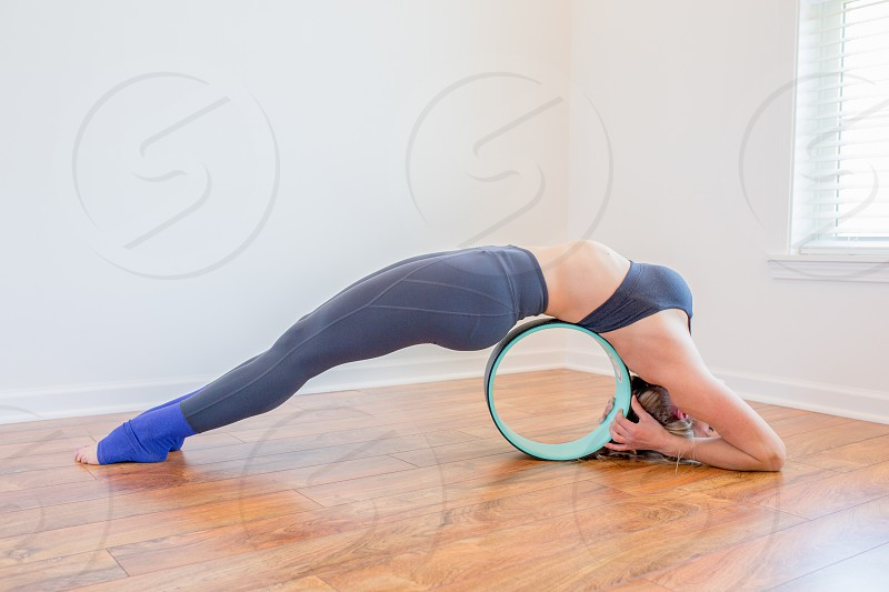 woman in black sports bra exercising on green and black ball photo