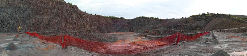 driller in a quarry mine. porphyry rocks. mining industry and red safety fence. photo made of 5 separate images. photo