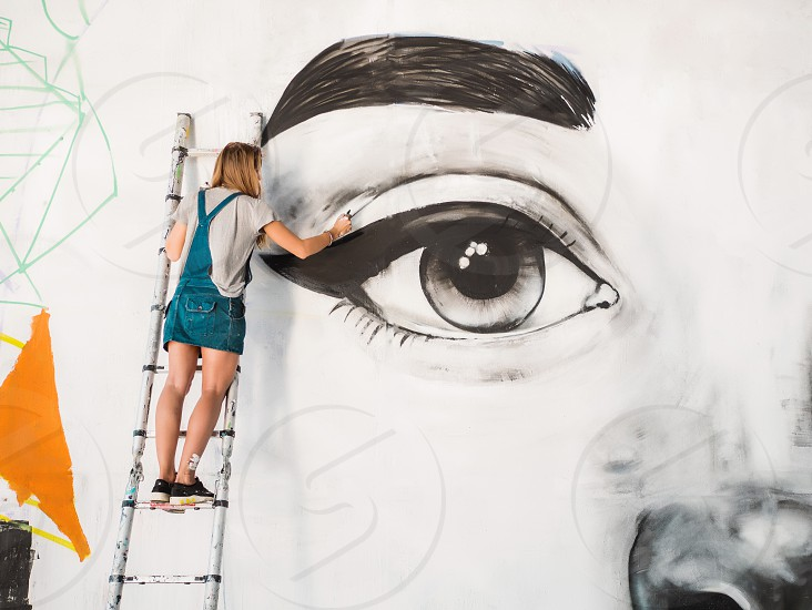 Graffiti Artist Drawing face of beautiful woman with paint on Street Wall. Female working with brush. Urban Outdoors Art Concept. photo